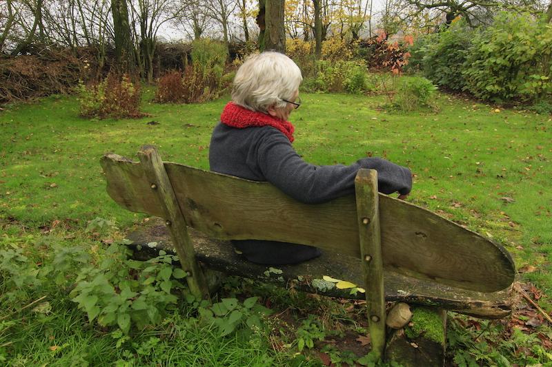 Alte Frau sitzt auf Bank